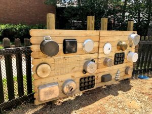 a wooden wall with pots and pans hanging on it - a music wall