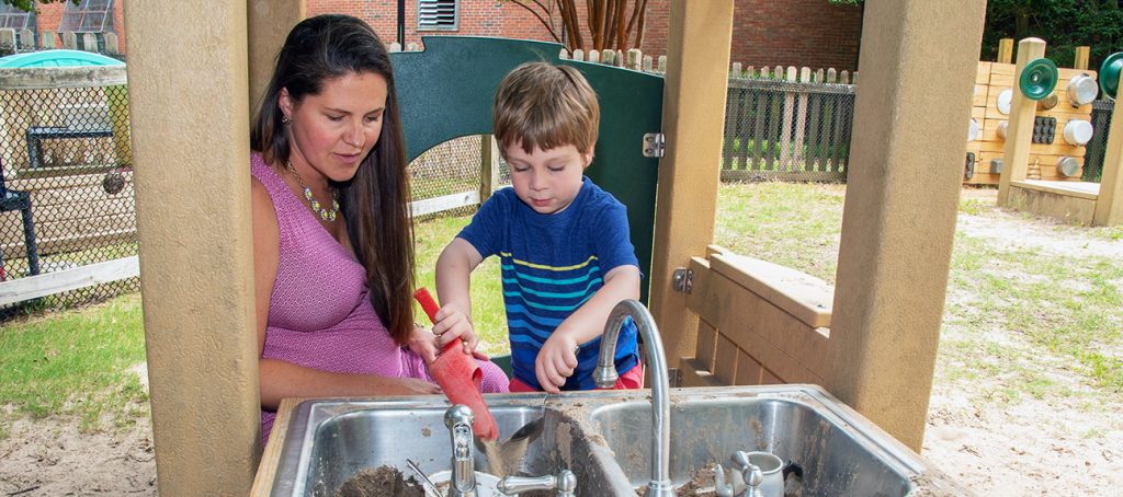 Teacher and student playing in a mud kitchen